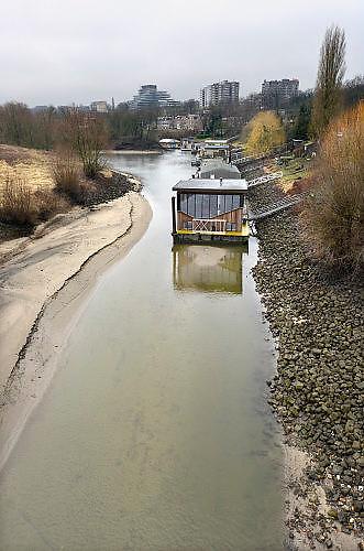 Nederland, Nijmegen, 30-1-2017De waterstand in de rivier de Waal is extreem laag voor de tijd van het jaar. Woonboten in een rivierarm in de buurt van de stad vallen bijna droog. Binnenvaartschepen nemen minder lading, vracht in en moeten goed in de vaargeul blijven.Foto: Flip Franssen