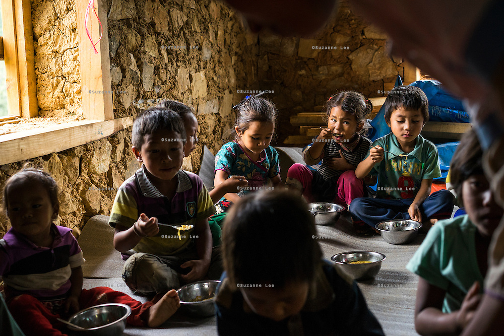 Children eat their lunch and care for each other in the SOS Children's Villages Child Care Space canteen in Rayale, Nepal on 1 July 2015. The Child Care Space was set up by SOS Children's Villages soon after the earthquake so that the children of the village can come together to play, learn, and get over the trauma of the disaster as well as get regular daily meals. This also allows their parents to be free to reconstruct their homes and go off to get rations and relief kits. Photo by Suzanne Lee for SOS Children's Villages