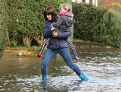 A young mother carries her daughter through a flooded street in the village of Bridge, Kent , United Kingdom. Sunday, 9th February 2014. Picture by Stephen Lock / i-Images