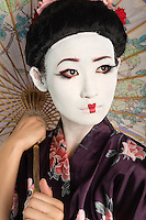 Close-up of Japanese woman with painted face holding parasol