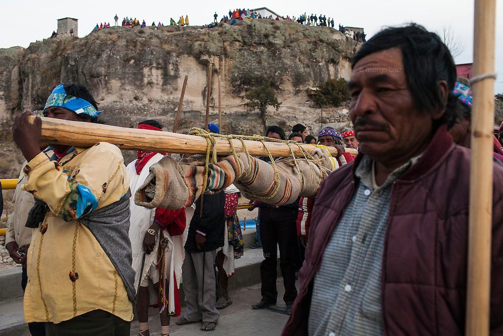 Un grupo de indígenas rarámuris acompañan la procesión al panteón cargando en hombros una figura de Cristo envuelto en una cobija amarrada a un tronco durante la festividad de Semana Santa en Norogachi, México, el 10 de abril de 2009.