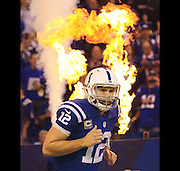 Indianapolis Colts quarterback Andrew Luck looks like he is on fire as he passes by flames coming onto the field for the game against the Jaguars. Indianapolis hosted Jacksonville at Lucas Oil Stadium on Sunday, November 23, 2014.