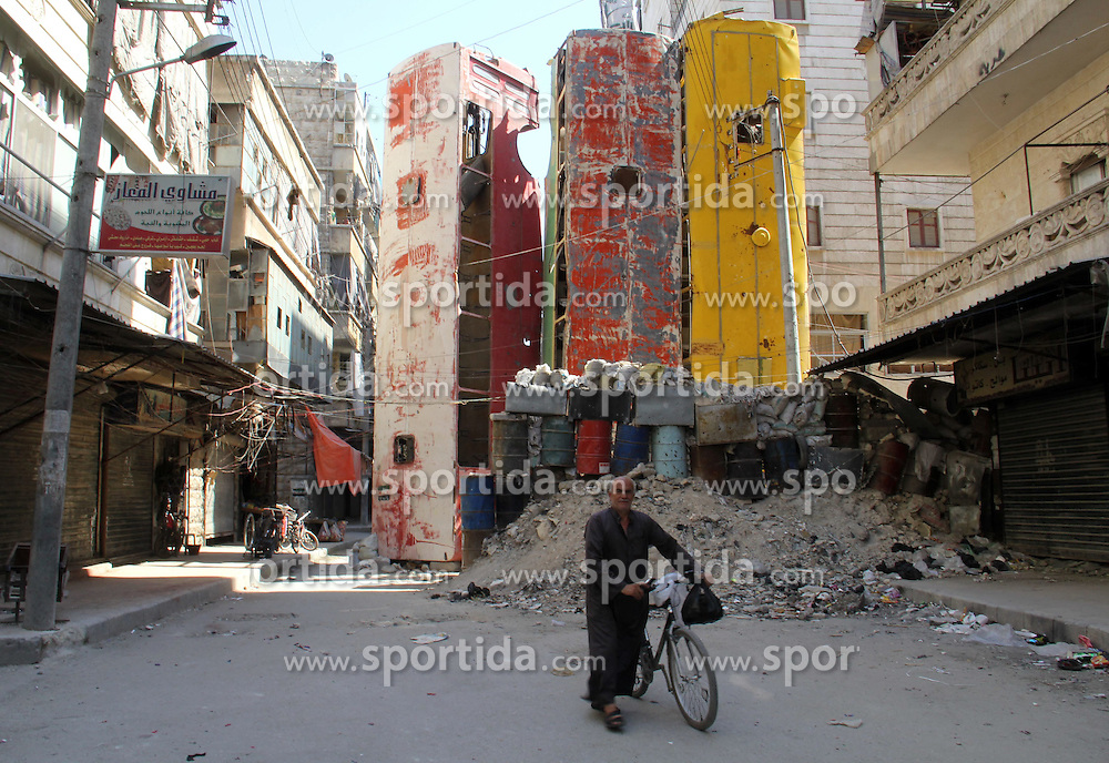 04.07.2015, Aleppo, SYR, B&uuml;rgerkrieg in Syrien, im Bild ein Mann spaziert mit seinem Fahrrad durch die zerst&ouml;rte Stadt // A Syrian man rides a bicycle at the street. The Syrians used the wreckage Buses, cars and concrete slabs to protect themselves from the snipers of Syrian regime forces, Syria on 2015/07/04. EXPA Pictures &copy; 2015, PhotoCredit: EXPA/ APAimages/ Ameer al-Halbi<br /> <br /> *****ATTENTION - for AUT, GER, SUI, ITA, POL, CRO, SRB only*****