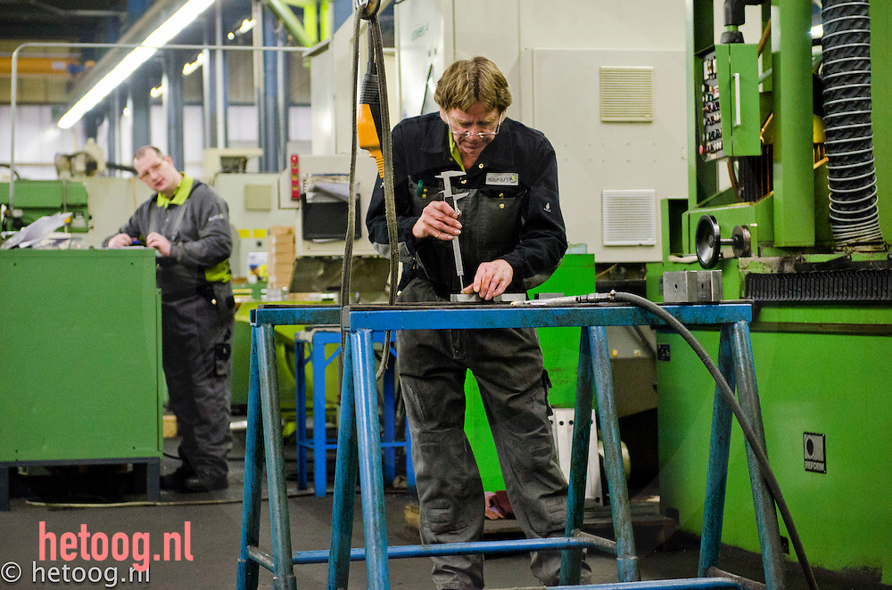 Nederland, Lochem,01feb2011 een werknemer meet de diepte van een boorgat bij werkbankfabrikant SAFAN
