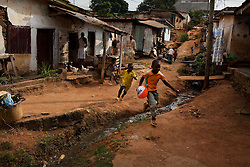 Kids play in the streets of a poor area in Yaounde, Cameroon. An open sewer runs through the community, but every saturday morning the locals gather to clean up their area. Yaounde, Cameroon.