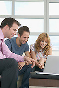 Real estate agent using laptop with couple in new home