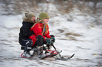 Arndís og Ari Carl renna sér á sleða á hólnum við Árbæjarkirkju.