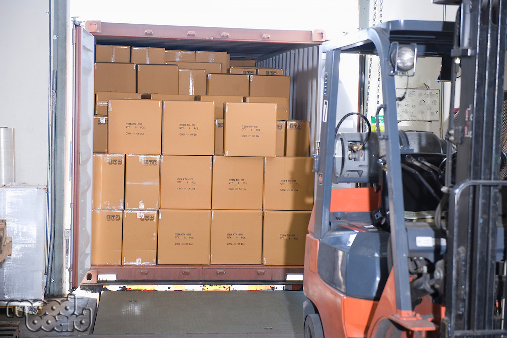 Cardboard boxes and fork lift truck in distribution warehouse