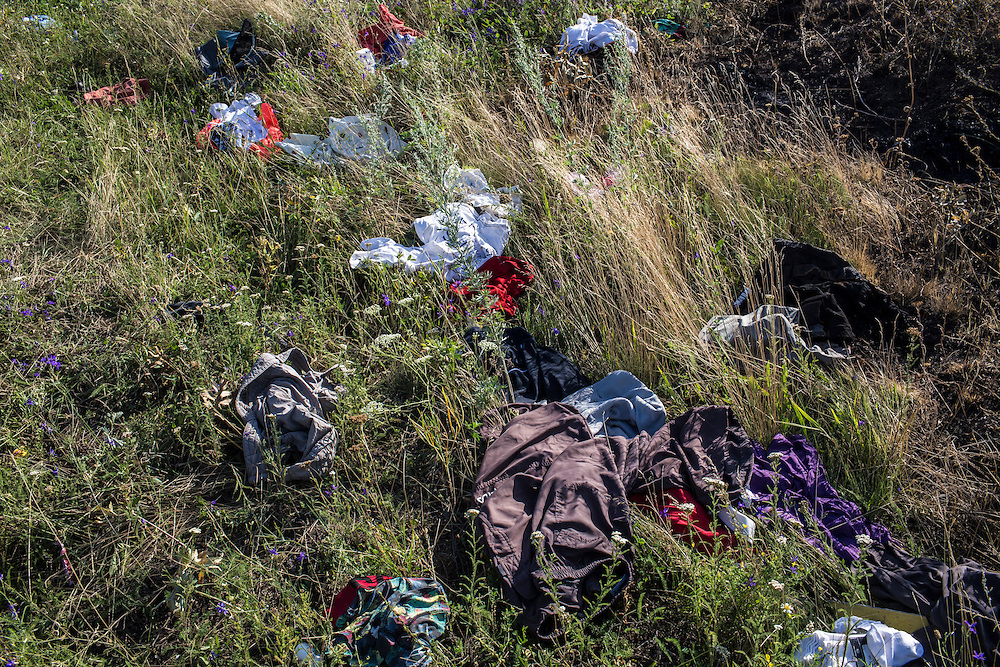 GRABOVO, UKRAINE - JULY 20: Clothing from the crash of Malaysia Airlines flight MH17 is strewn in the grass at the crash site on July 20, 2014 in Grabovo, Ukraine. Malaysia Airlines flight MH17 was travelling from Amsterdam to Kuala Lumpur when it crashed killing all 298 on board including 80 children. The aircraft was allegedly shot down by a missile and investigations continue over the perpetrators of the attack. (Photo by Brendan Hoffman/Getty Images) *** Local Caption ***