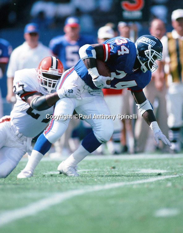 New York Giants running back Herschel Walker (34) tries to break a tackle by Cleveland Browns safety Stevon Moore  (27) as he runs the ball during the NFL preseason football game against the Cleveland Browns on Aug. 6, 1995 in Cleveland. The Giants won the game 19-13. (©Paul Anthony Spinelli)