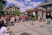 Entertainer in Whistler village rides a unicycle while juggling fire batons on a summer day.