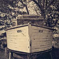 Bow view of an old holiday cruiser moored on dry land under trees
