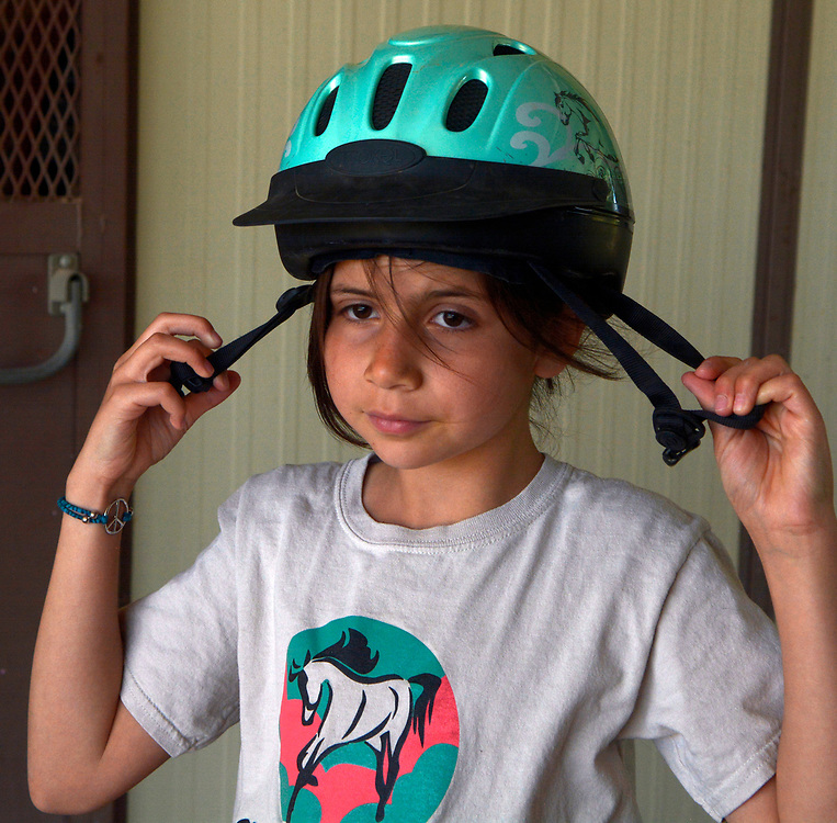 "gbs050717y/LIVING -- Esmeralda  ""Esme""  Marquez-Chavez, 9, of Albuquerque, puts on her helmet before  horse vaulting  practice.(Greg Sorber/Albuquerque Journal)"