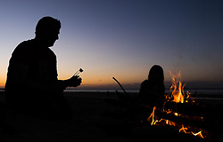 © Licensed to London News Pictures.27/08/15<br /> Saltburn, UK. <br /> <br /> NEIL WHITTLE and his daughter Mia, 6, form Saltburn roast marshmallows over a fire as they enjoy the sunset on the beach.<br /> <br /> Photo credit : Ian Forsyth/LNP