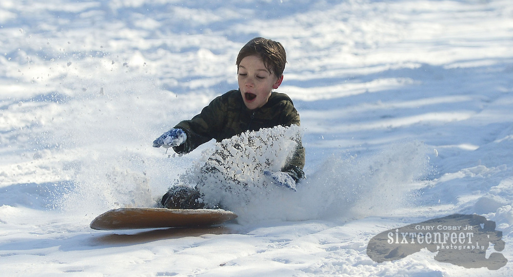 Gary Cosby Jr./Decatur Daily   Snow blankets the Tennessee Valley Thursday morning after a snow that began late Wednesday and fell through much of the night.  Nathan Burleson throws up a rooster tail of snow as he sleds down a hill on Colony Lane in Hartselle.