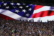 Fans in silhouette raise their hands and cheer with a large American flag displayed on the scoreboard before the Pittsburgh Steelers 2016 NFL week 1 regular season football game against the Washington Redskins on Monday, Sept. 12, 2016 in Landover, Md. The Steelers won the game 38-16. (©Paul Anthony Spinelli)
