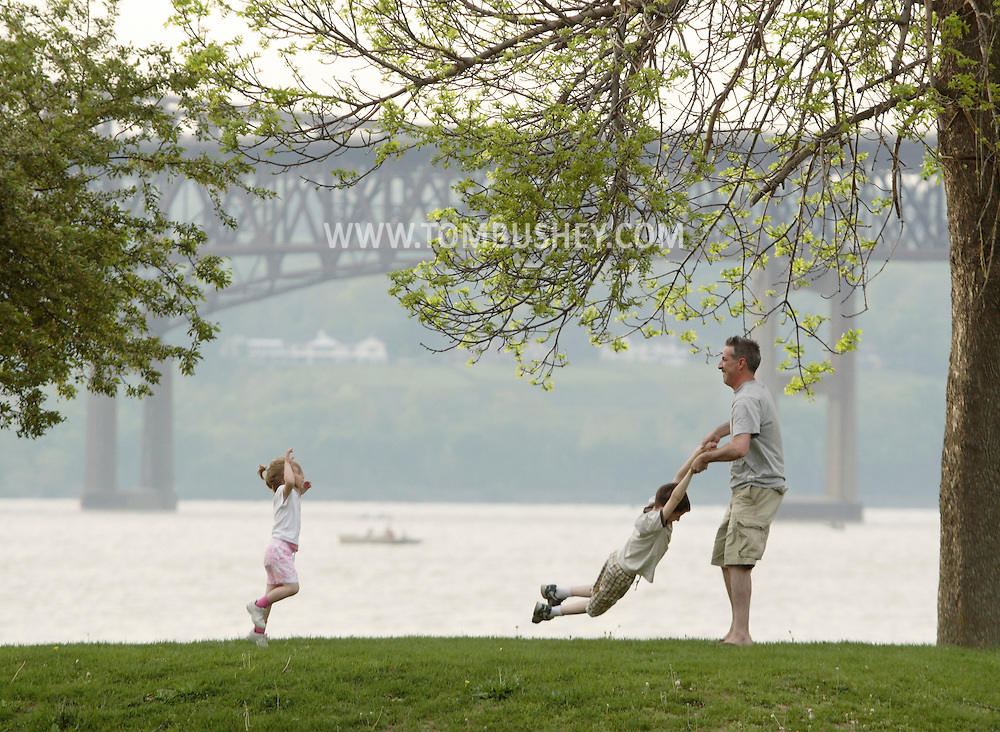 Beacon, New York - A man lifts swings a little boy by his hands while a girl watches at a Hudson River waterfront park on May 1, 2010. The Newburgh Beacon Bridge is in the background.