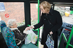 Volunteer carer handing shopping to client on a trip organised by a resource for people with physical and sensory impairment.
