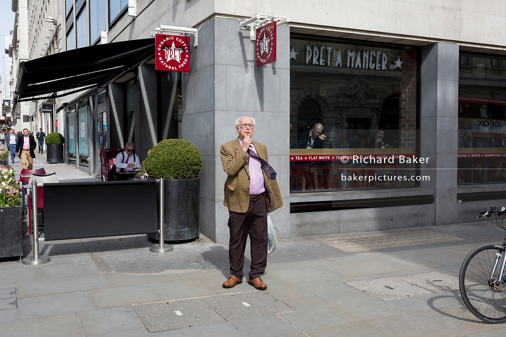 An elderly man vapes on the corner of a central London street, on 6th April 2018, in London, England.