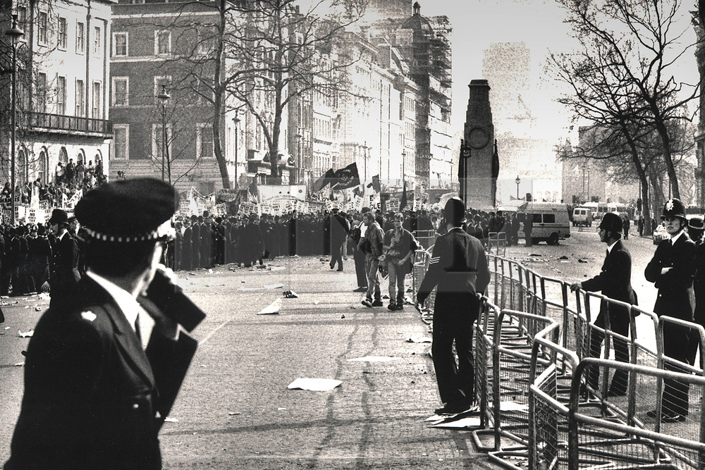 © Licensed to London News Pictures. 25/03/2020. London, UK. In this image from March 31st 1990 police surround protesters on Whitehall near the Cenotaph during the London poll tax riots. The protest on the last day of March in 1990 started peacefully when thousands gathered in a south London park to demonstrate against Margaret Thatcher's Government's introduction of the Community Charge - commonly known as the poll tax. Marchers walked to Whitehall and Trafalgar Square where violence broke out with the trouble spreading up through Charring Cross Road and on to the West End. Police estimated that 200,000 people had joined the protest and 339 were arrested. The hated tax was eventually replaced by the Council Tax under John Major's government in 1992.  Photo credit: Peter Macdiarmid/LNP