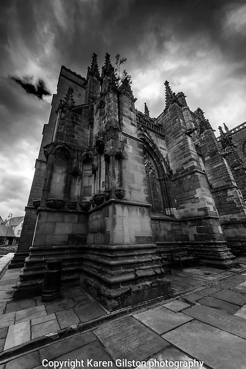 B&W image of Chester cathedral showing exterior elevation, architectural details, and surrounding graveyard stones.