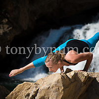 dramatic hand balance  yoga pose on boulder in front of a large waterfall