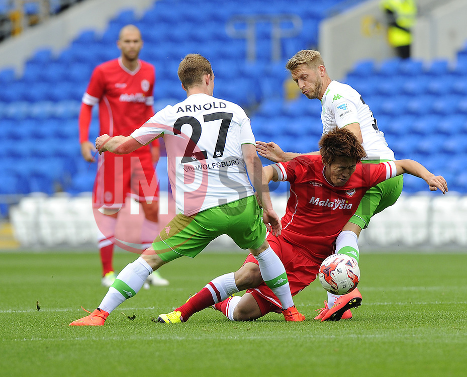 Cardiff City's Kim Bo Kyung is fouled by VfL Wolfsburg's Maximilian Arnold and VfL Wolfsburg's Aaron Hunt - Photo mandatory by-line: Joe Meredith/JMP - Mobile: 07966 386802 02/08/2014 - SPORT - FOOTBALL - Cardiff - Cardiff City Stadium - Cardiff City v VfL Wolfsburg - Pre-Season Friendly