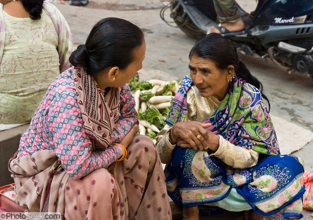 """Two women sell vegetables on the street in Kathmandu (sometimes called """"Kantipur""""), the largest city in Nepal (population 700,000). The original inhabitants are Newars, who speak the language Nepal Bhasa. However, Nepali is the lingua franca of the valley and is the most widely spoken language in this country of diverse ethnic groups, who speak somewhere between 24 to 100 different languages and dialects. The city stands at an elevation of 6235 feet / 2230 meters."""