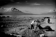 Guatemalan man earns a meager living selling gravel and stone obtained by hard labor from this highland riverbed, Lago Atitlan, Guatemala.  According to the World Bank (2007), the average Guatemalan earns US$2,400 per year, a figure probably unattainable selling gravel for building construction.  So, far better wages are possible for those who can cross to the United States.