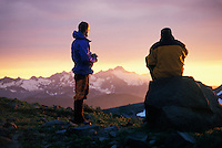 Mountain Climbers in the Washington Cascades watching a sunset.  Mount Baker, Washington, USA<br />