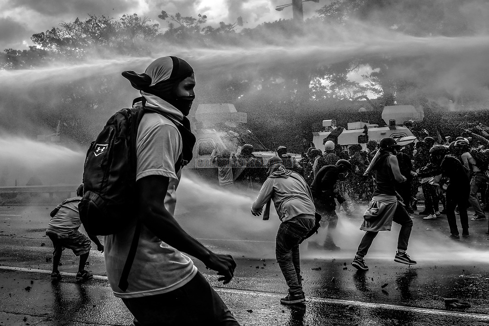 Caracas, Venezuela - 1/5/17: Protesters are leading another day of protests and are blocked and dispersed with watercannon and tear gas thrown by the National Guard. They try to march to the National Electoral Council (CNE) and the Supreme Court of Justice, demand release of political prisoners, restitution of powers to the National Assembly and electoral timetable. (Photography: Gregorio Marrero)