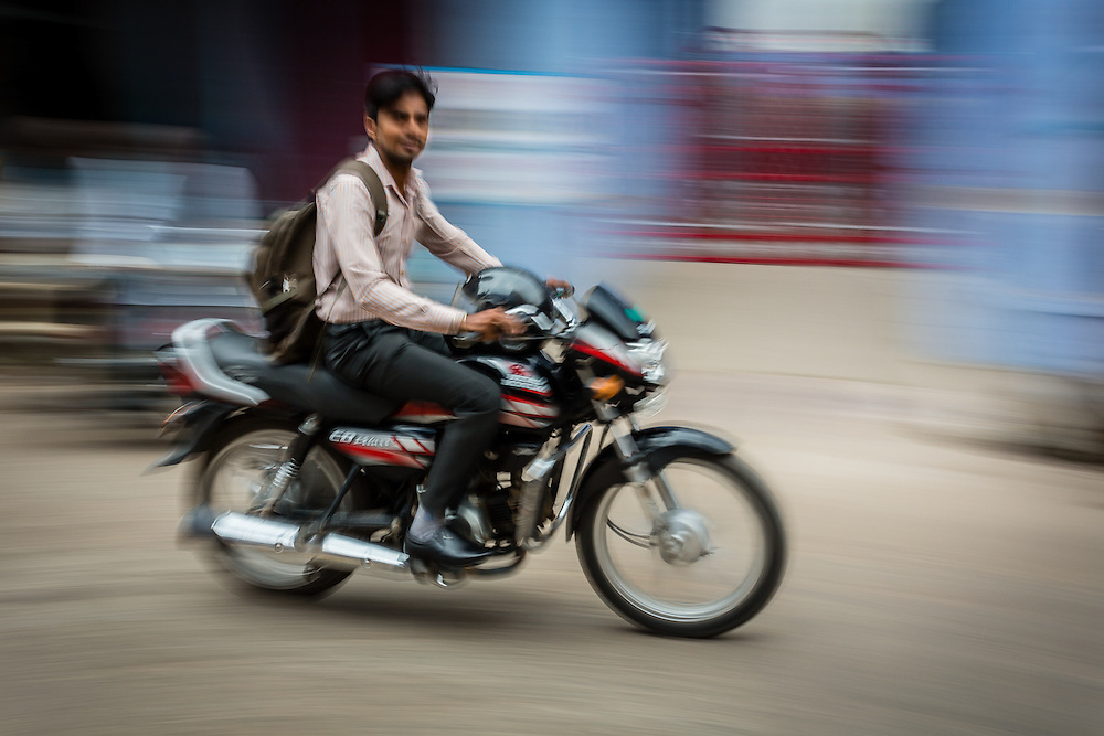 A panning shot of a man riding his motorbike