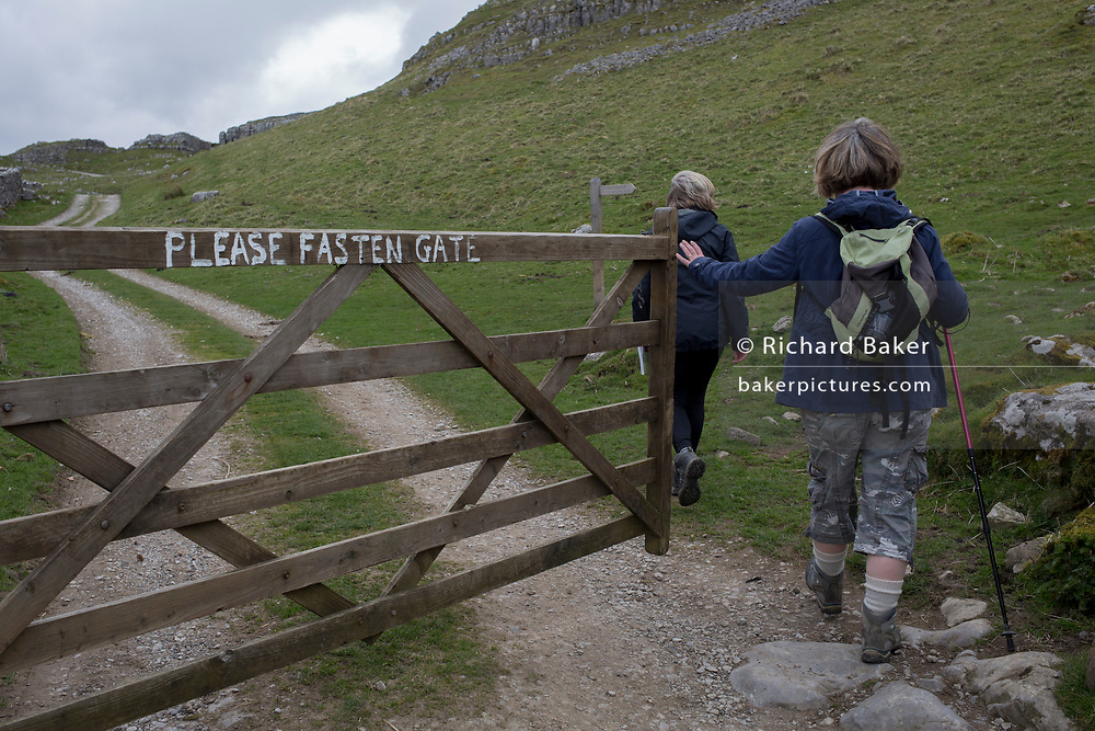 Walkers open a farmer's gate and enter a field while keeping to a public footpath on 13th April 2017, in Settle, Yorkshire, England.