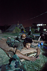© Licensed to London News Pictures. 29/06/2014. Khanaqin, UK  Khanaqin, Iraq. A Kurdish peshmerga checks his mobile phone before sleeping at a Kurdish peshmerga base in Khanaqin, Iraq.<br /> <br /> The peshmerga, roughly translated as those who fight, is at present engaged in fighting ISIS all along the borders of the relatively safe semi-automatous province of Iraqi-Kurdistan. Though a well organised and experienced fighting force they are currently facing ISIS insurgents armed with superior armament taken from the Iraqi Army after they retreated on several fronts. Photo credit : Matt Cetti-Roberts/LNP