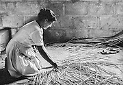 Vicenta Vasquez weaves a straw mat in the rural mountain village of El Limon, Honduras.