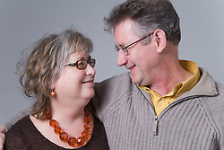 Portrait of a middle aged couple smiling at one another,