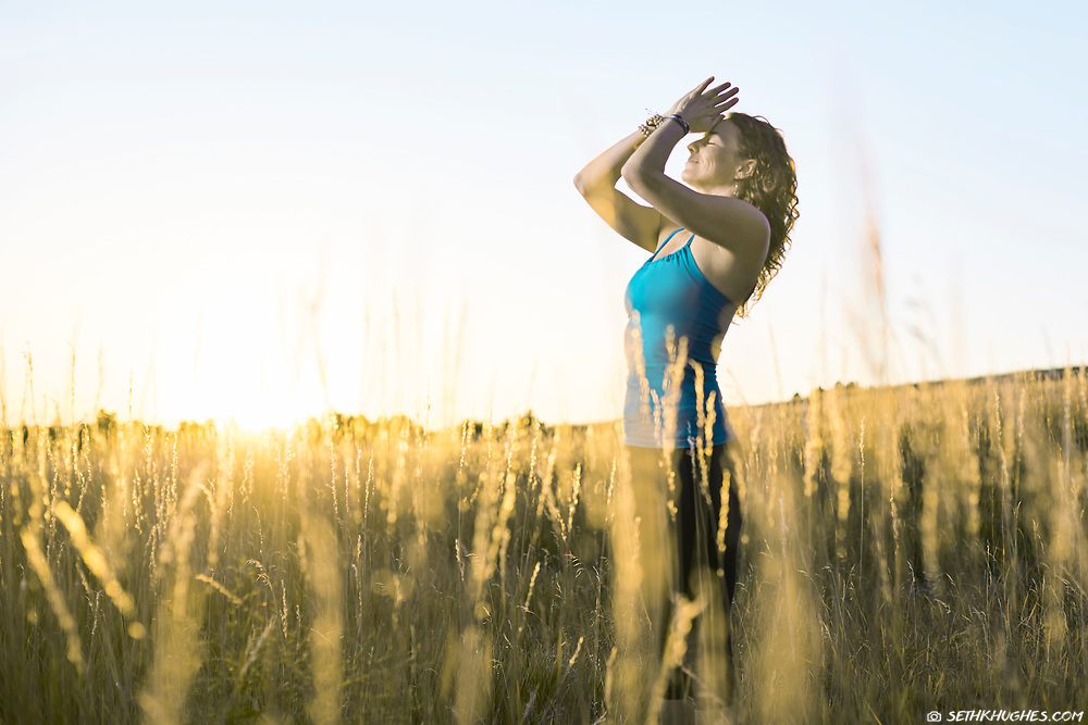 Practicing yoga and gratitude in a field during early morning sunrise.
