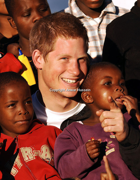 Prince Harry cuddles children Mutsu (left) and Lintle (right), in the grounds of the Mants'ase children's home, while on a return visit to Lesotho in southern Africa on Monday April 24 2006. The Prince was in the country to launch his new charity called 'Sentebale', which means 'Forget me not' in memory of his mother Diana Princess of Wales. .