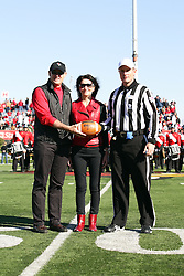 15 October 2011: Referee Kerry Ripley is presented the game ball by a pair of Redbird supports during an NCAA football game between the University of South Dakota Coyotes and the Illinois State Redbirds (ISU) at Hancock Stadium in Normal Illinois.