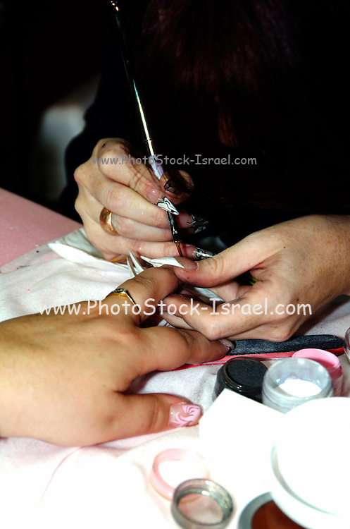 Manicurist takes care of womans fingernails, painting a design on the nail