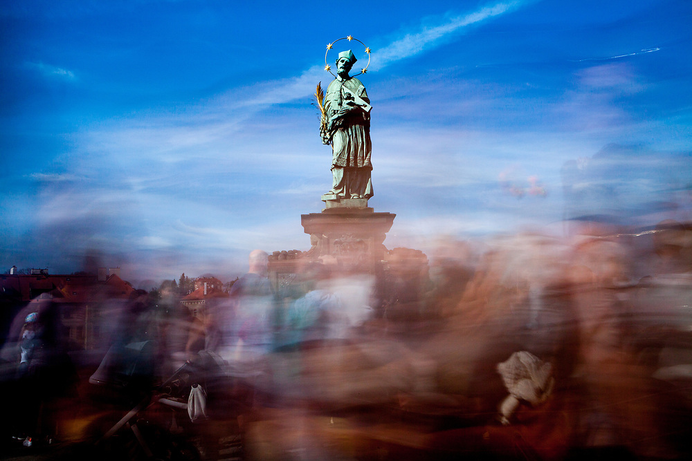 "Crowds are passing the statue of  ""John of Nepomuk"" which is an outdoor sculpture, installed in 1683 on the north side of the Charles Bridge in Prague, Czech Republic."