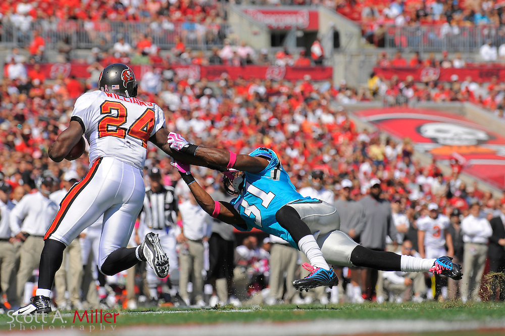 Oct 18, 2009; Tampa, FL, USA; Tampa Bay Buccaneers running back Carnell Williams (24) is tackled by Carolina Panthers cornerback Richard Marshall (31) during the first quarter of their game at Raymond James Stadium. ©2009 Scott A. Miller