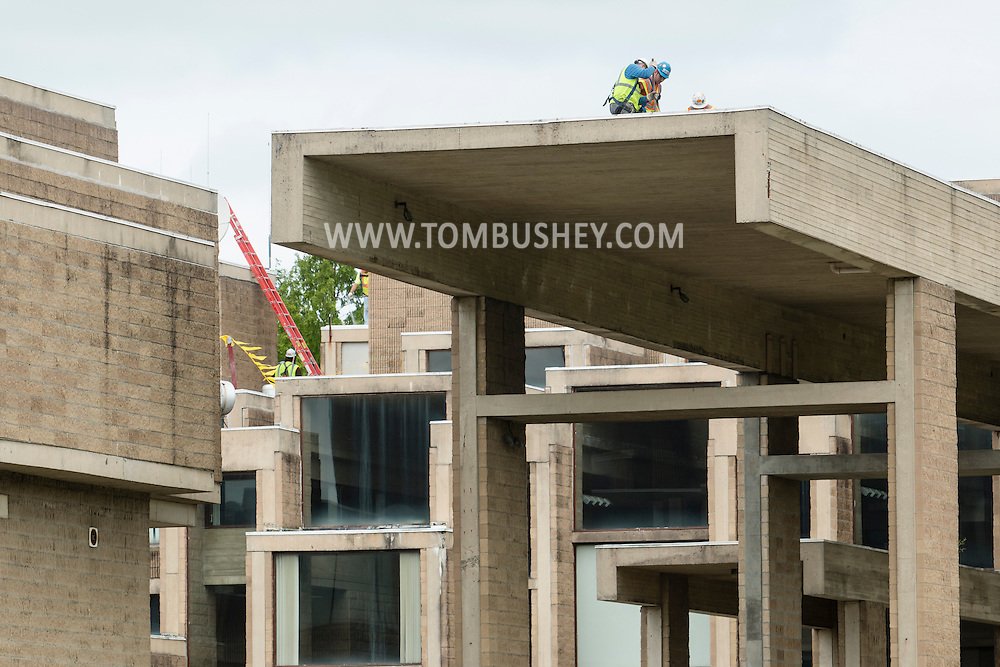 Goshen, New York - Men work of the roof of the closed Orange County Government Center on May 20, 2015. The building, which has been closed because of water damage since 2011, is going to be renovated and partially demolished. The building was designed in the brutalist style by noted architect and dean of the Yale School of Architecture Paul Rudolph in 1963 and built in 1967.