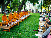 "17 MARCH 2018 - BANGKOK, THAILAND:  Buddhist monks lead a prayer during a ""sticky rice merit making"" in Lumpini Park in Bangkok. Sticky rice merit making is a merit making in the Isan / Lao style, when people present small amounts of cooked sticky rice (also known as glutinous rice) to Buddhist monks. Isan is the northeast region of Thailand.    PHOTO BY JACK KURTZ"