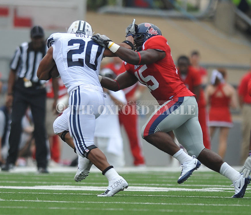 BYU's Chase Pendley (20) is tackled by Ole Miss' Joel Kight (15) at Vaught-Hemingway Stadium in Oxford, Miss. on Saturday, September 3, 2011. BYU won 14-13.
