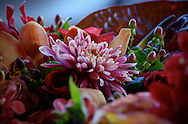 Warm red, peach, orange and gold tones fill an autumn bouquet of roses, orchids and bright fall leaves.