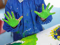Boy finger painting in art class mid section