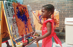 Nursery school girl wearing apron painting at easel in playground,