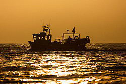 © Licensed to London News Pictures. 12/11/2018. Scarborough UK. Fisherman return to Scarborough harbour at sunrise this morning on the Yorkshire coast. Photo credit: Andrew McCaren/LNP
