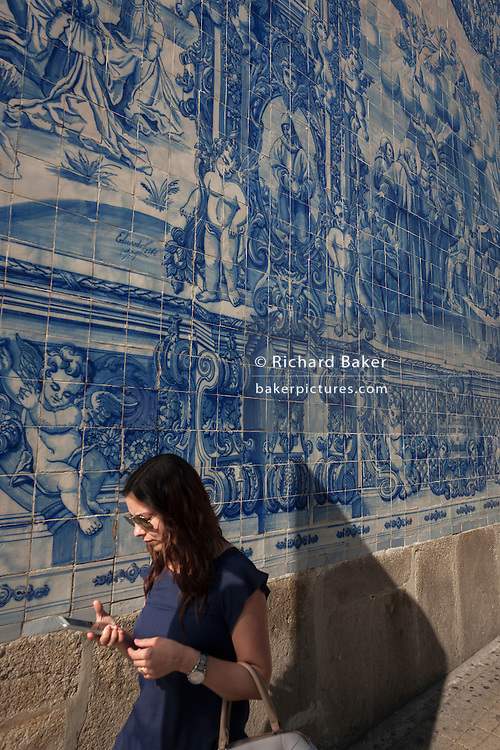 A young woman uses her phone beneath traditional Azulejo tiles on the wall of Capela Das Almas (church), on Rua Santa Catarina Porto, Portugal. The panels depict scenes from the lives of various saints including the death of St Francis and the martyrdom of St Catherine. Eduardo Leite painted the tiles in a classic 18th-century style, though they actually date back only to the early 20th century.
